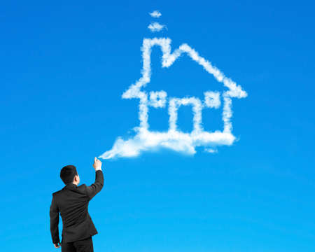 Businessman spraying house shape cloud paint with blue sky background photo