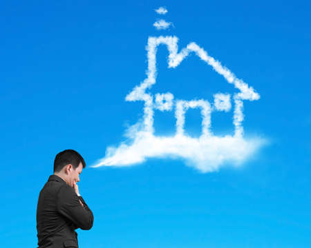 Businessman thinking about house shape cloud with blue sky background
