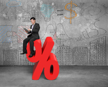 percentage sign: Using tablet businessman sitting on red percentage sign with business concept doodles wall background