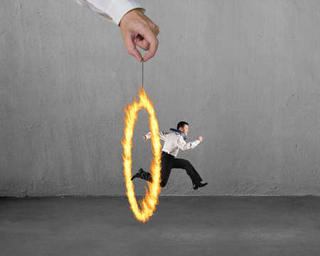 Man jumping through fire circle hand holding with concrete wall background photo