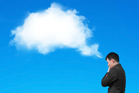 Businessman thinking about white cloud thought bubble above his head isolated on blue background