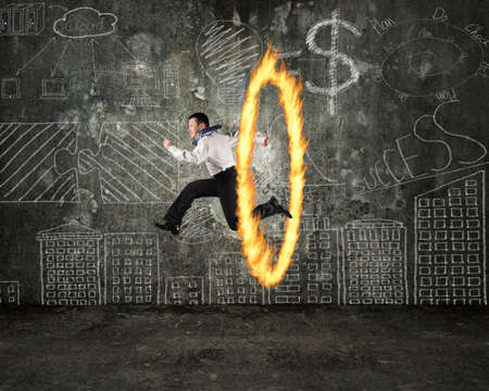 Man jumping through fire hoop with doodles wall background photo
