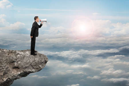 businessman using a megaphone: Businessman using megaphone yelling on cliff with sunlight cloudscape background