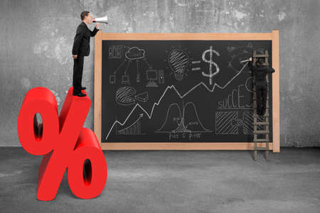 concrete room: Businessman using megaphone standing on red percentage sign with business concept doodles and concrete room blackboard