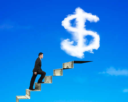 upward struggle: Businessman climbing on money stairs with dollar sign shape cloud on blue sky background Stock Photo