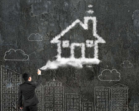 Businessman spraying house shape cloud paint with cityscape doodles wall background photo