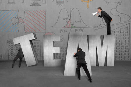 Businessman using megaphone commanding employees to move TEAM 3D concrete word together with doodles wall background