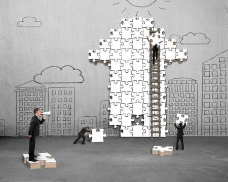 Businessman using megaphone commanding workers to build arrow jigsaw puzzle with doodles concrete wall background