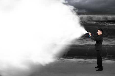 Business man spraying white cloud paint covered dark stormy ocean background