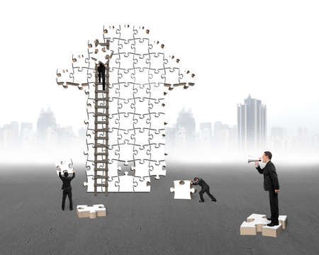 businessman using a megaphone: Businessman using megaphone commanding workers to build arrow jigsaw puzzle with gray ground cityscape background Stock Photo