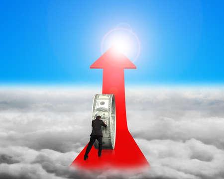 upward struggle: Businessman pushing money circle on red arrow with blue sky sunlight cloudscape background