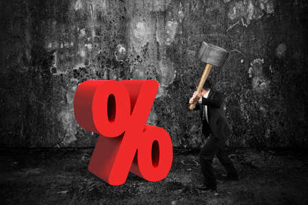 down beat: Businessman holding sledgehammer hitting red percentage sign with dark concrete room background