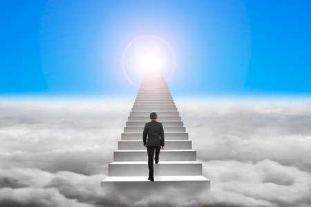 upward struggle: Businessman climbing the concrete stairs with blue sky sunlight cloudscape background