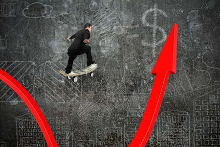 Businessman skateboarding on red growing arrow graph with doodles wall background photo