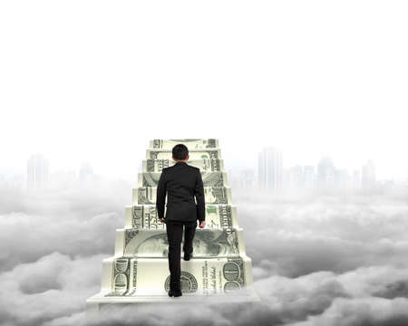 dollar: Businessman climbing the money stairs with gray cityscape cloudscape background