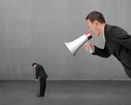 concrete room: Businessman using megaphone yelling at his employee with concrete room background Stock Photo