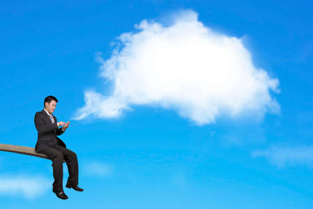 springplank: Gebruik van mobiele telefoon zakenman zittend op springplank met witte wolk gedachte bubble en de blauwe hemel achtergrond