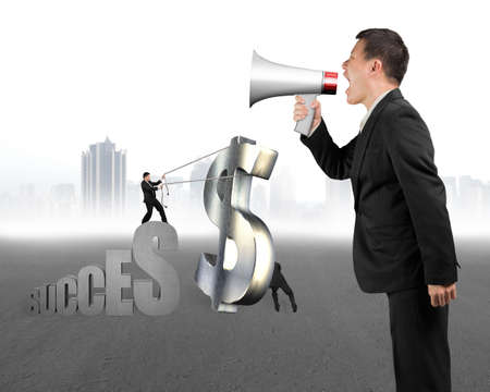 businessman using a megaphone: Businessman using megaphone to command employees moving metal dollar sign with cityscape background