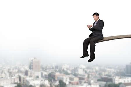 springplank: Met behulp van mobiele telefoon zakenman zittend op springplank met stadsbeeld achtergrond