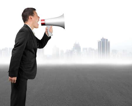 megafono: Hombre de negocios que usa el megáfono gritando con paisaje urbano de fondo gris Foto de archivo