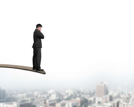ideas risk: Thinking businessman standing on springboard with cityscape background