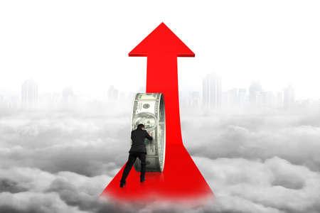 upward struggle: Businessman pushing money circle on red arrow with cityscape cloudscape background Stock Photo