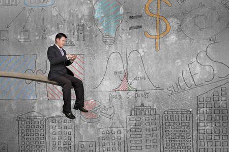 springplank: Met behulp van mobiele telefoon zakenman zittend op springplank met doodles muur achtergrond