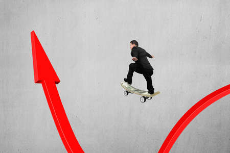 Businessman skateboarding on red arrow pointing up with concrete wall background photo
