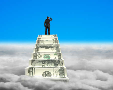looking around: Businessman reaching the top of money stairs looking around blue sky with cloudscape background
