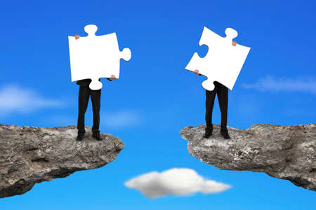 copartnership: Businessmen holding two white jigsaw puzzles to connect on the cliff with sky background