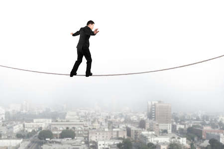risky job: Businessman balancing and walking on the rope high in the sky with urban scene background