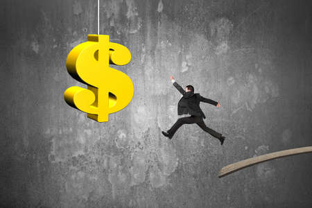 Businessman jumping from wooden board to golden dollar sign with concrete wall background Banco de Imagens