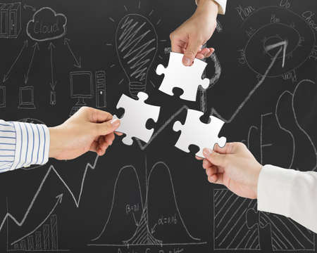 Group of business people assembling blank white jigsaw puzzles on business concept doodles background