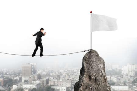 balanza: Empresario caminar y mantener el equilibrio sobre la cuerda hacia la bandera blanca de la cima de la montaña con el fondo del paisaje urbano