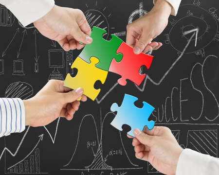 Group of business people assembling colorful jigsaw puzzles on business concept doodles background