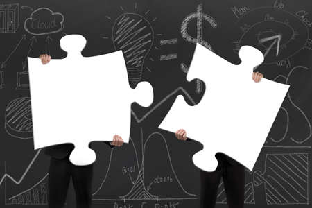copartnership: Two business people assembling blank white jigsaw puzzles on business concept doodles background Stock Photo