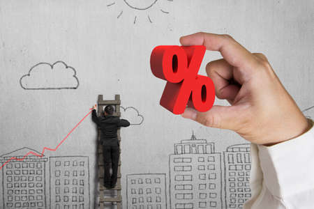 Hand holding 3D red percentage sign with businessman drawing trend chart on doodles wall background