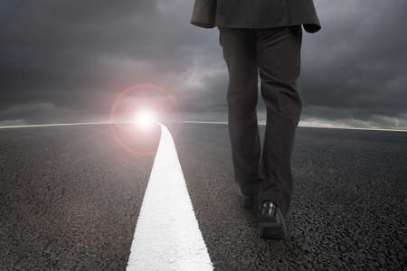Businessman walking on asphalt road with white line and sunlight cloudy sky Stock Photo