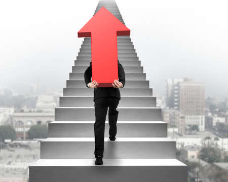 hard work ahead: Businessman carrying big 3D red arrow sign and climbing on concrete stairs with urban scene background Stock Photo
