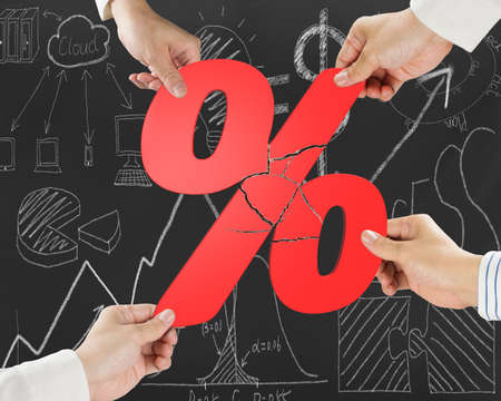 broken unity: Group of business people assembling broken red percentage sign with doodles background Stock Photo