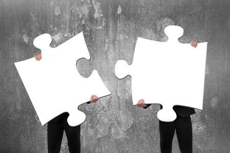 적합: 콘크리트 벽을 배경으로 빈 흰색 직소 퍼즐을 조립하는 두 비즈니스 사람