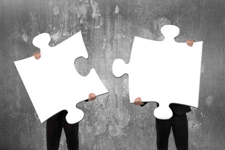 Two business people assembling blank white jigsaw puzzles with concrete wall background Фото со стока