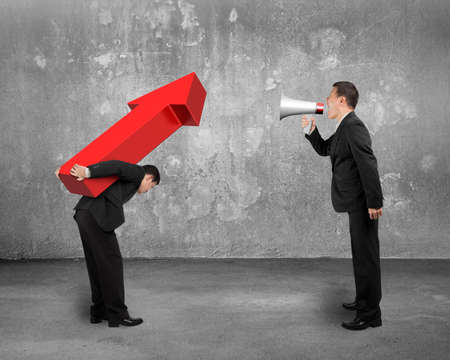 Boss using megaphone shouting at employee carrying big 3D red arrow sign with concrete room background photo