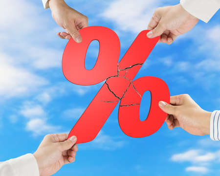 synergism: Group of business people assembling broken red percentage sign with sky background Stock Photo