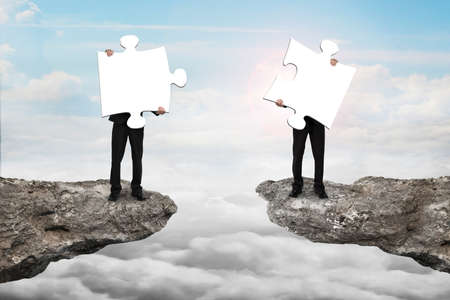 copartnership: Businessmen holding two white jigsaw puzzles to connect on the cliff with cloudscape sunlight background Stock Photo