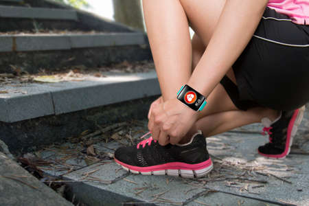 salud: Mujer del deporte mano atarse los cordones que llevan SmartWatch de pantalla táctil con sensor de APP de salud icono en el fondo pista forestal