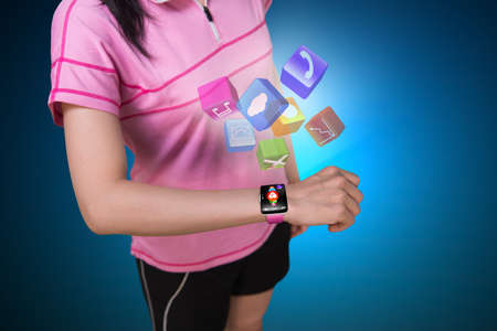 Sport woman wearing touchscreen smartwatch with colorful app icons isolated on blue background Stockfoto