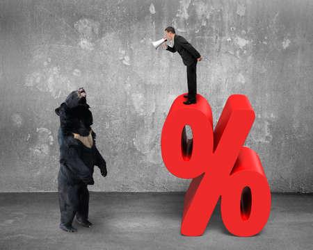 oso negro: Hombre de negocios usando el megáfono gritando a oso negro en signo de porcentaje rojo con muro de hormigón y el fondo piso