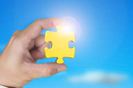 puzzling: Hand holding gold jigsaw puzzle piece with blue sky sunlight background