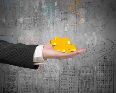 puzzling: Hand showing gold jigsaw puzzle piece with business concept doodles wall background